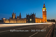 Cars drive past at twilight along the Westminster Bridge, Big Ben and the Houses of Parliament in London, England.