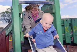 Single mother pushing young son down slide in playground,