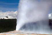 A raven flies past the Old Faithful geyser as it erupts in Yellowstone National Park, Wyoming. When Old Faithful erupts, it can launch as much as 8,400 gallons (32,000 liters) of boiling water as high as 185 feet (56 meters), although the average eruption height is 145 feet (44 meters). The time between eruptions is growing longer on average, possibly because earthquakes have affected underground water levels. The current interval is either 65 or 91 minutes depending on attributes of the prior eruption.