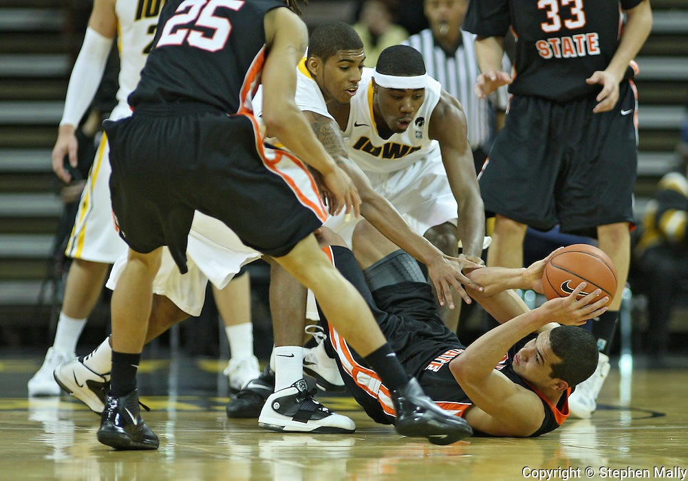 December 04 2010: Idaho State Bengals forward/center Abner Moreira (21) pulls in a lose ball as Iowa Hawkeyes guard/forward Roy Devyn Marble (4) and forward Melsahn Basabe (1) try to grab it during the first half of their NCAA basketball game at Carver-Hawkeye Arena in Iowa City, Iowa on December 4, 2010. Iowa won 70-53.