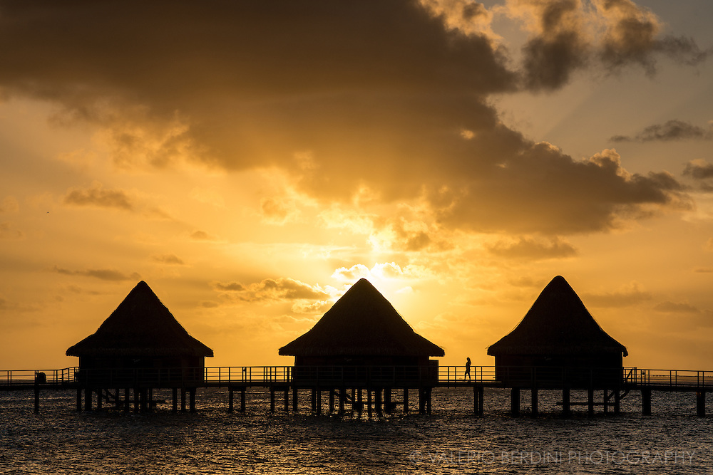 """Sunset over a row of luxury """"overwater"""" bungalows in Rangiroa atoll"""