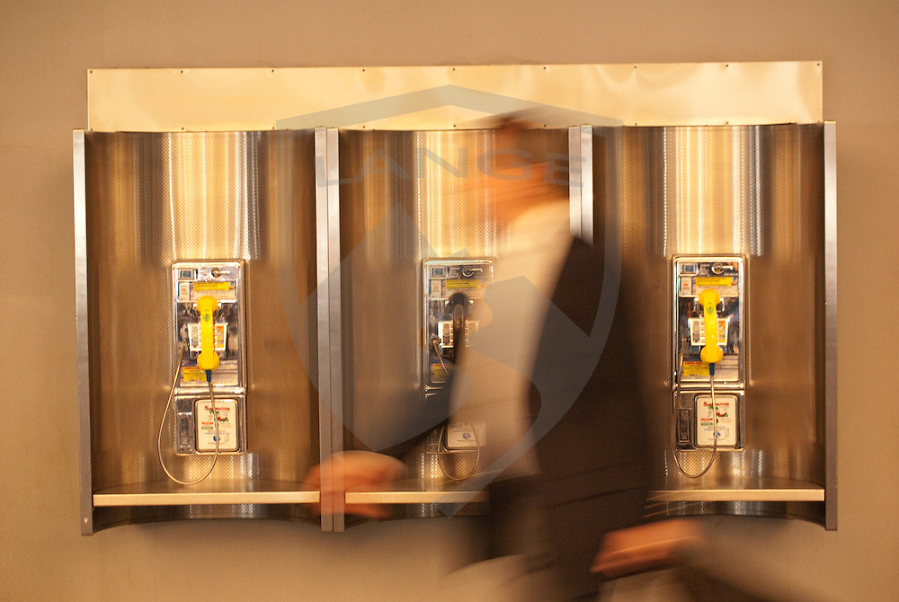 pay phone telephones and man passing by in blurred motion at the george bush international airport in Houston, texas, usa.