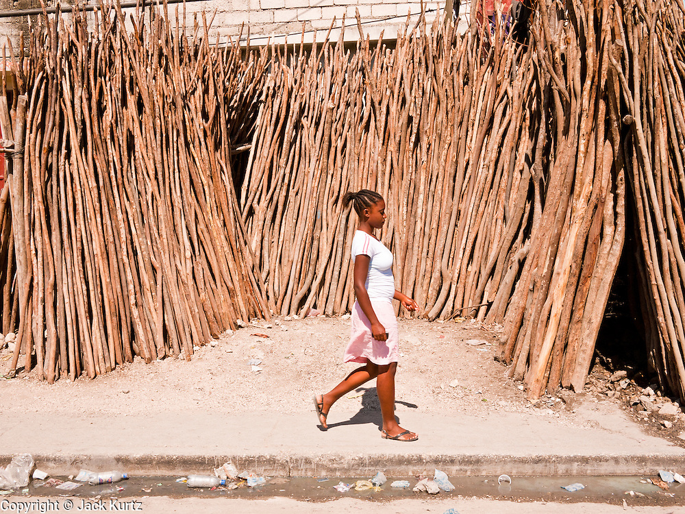 17 NOVEMBER 2010 - PORT-AU-PRINCE, HAITI: A woman walks past a stand selling wooden posts in Port-au-Prince. The posts are used to reinforce construction in Port-au-Prince. The city was devastated by an earthquake in Jan 2010 and has yet to be rebuilt. PHOTO BY JACK KURTZ