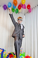 Cheerful young boy with raised fist in birthday party
