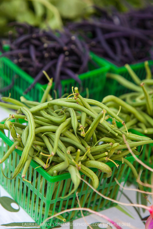Baskets of green and purple beans at a farmers' market,