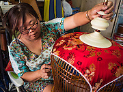 "08 FEBRUARY 2017 - BANGKOK, THAILAND: A woman does detail work on the artisan bird cages she and her husband make in their home in Pom Mahakan. The residents of the old fort are known for their community of song bird enthusiasts and artisan bird cage makers. More than 40 families still live in Pom Mahakan, a slum community in a 19th century fort in Bangkok. City officials are trying to move them out of the fort but members of the community refuse to leave. NGOs and historic preservation organizations are working with the community to help them find a way to stay. After several deadlines passed, residents were told that they have to leave by the end of February. They submitted another proposal to the city this week to turn their community into a ""living heritage museum"" and hope to get the eviction deadline extended until late March.       PHOTO BY JACK KURTZ"