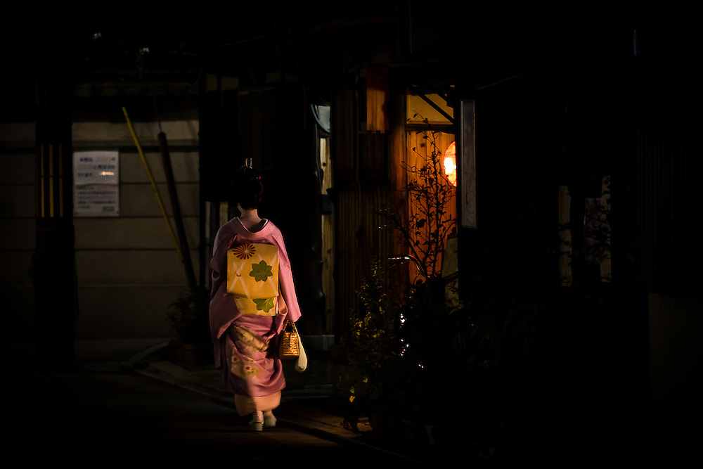 A maiko (apprentice geisha) on her way to entertain guests in a tea-house, passes by the lit entrance to a house in the district of Gion, Kyoto.