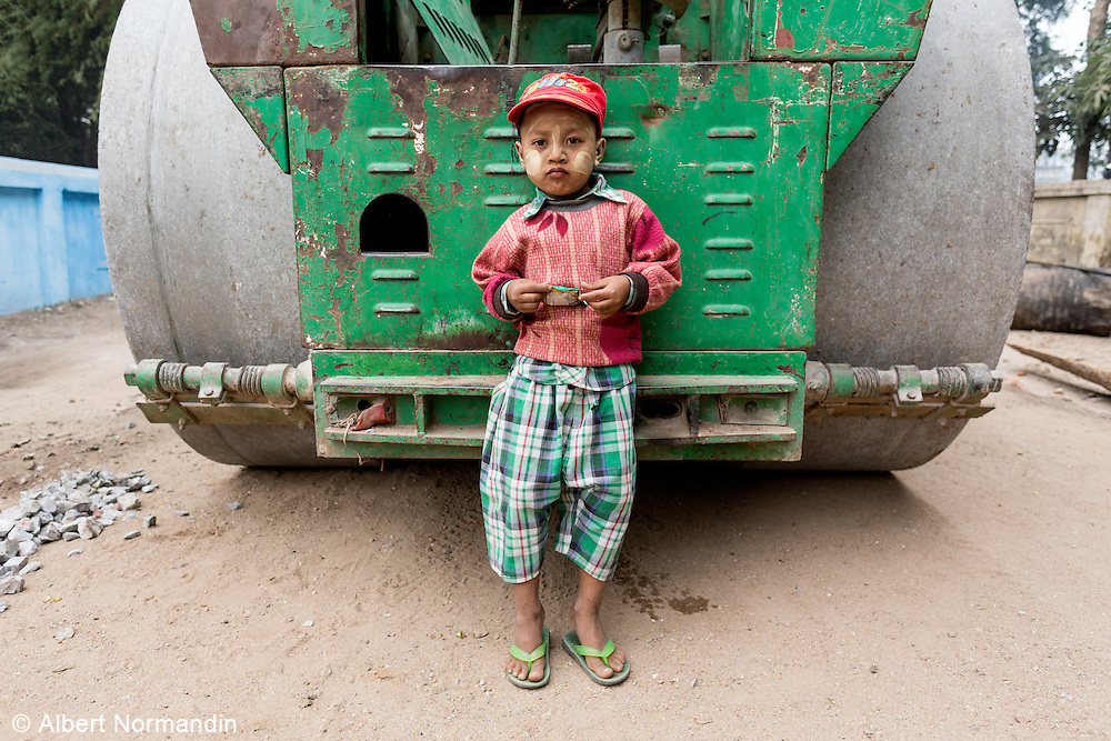 Young boy at rear of road paving equipment with steel wheels, Hsipaw