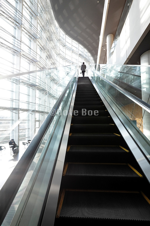 long escalator with male person at the top at the The National Art Center Tokyo Japan