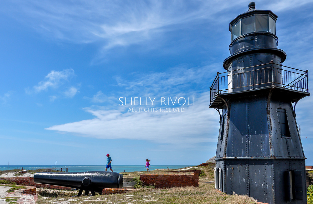 A father and daughter explore the roof of Fort Jefferson at Dry Tortugas National Park with lighthouse and cannon, water in background. Model released photo.