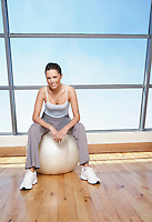 Woman sitting on Exercise Ball in gym portrait