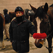 "Ernesto Cancino, 64, who has been a ponyboy who escorts the Thoroughbreds to the start at the Aqueduct racetrack in New York City since 1989, stands underneath the grandstand on a cold day, February 15, 2007. Before that he was a jockey in Chile, where he started riding horses on his father's farm at the age of 14. He says he loves the horses and the cold does not bother him, even half a century later. ""The body-I've got it ready all day,"" he says. ""A little hot coffee, it's fine.""..Betting on the horses is still a popular game and the money still flows, but off track betting and other forms of entertainment have eroded live attendance at the races.  The daily diehard betters and horse lovers who sparsely populate the place on work days are joined by a bigger crowd on the weekends. ..The Aqueduct, located in Ozone Park, Queens, is the only horse racing track in New York City and probably the coldest in the country (most of the others are in Kentucky, Florida or California). Horses race on the winterized inner dirt rack from January 1st through the end of April. Aqueduct was built in 1894, renovated in 1959, then opened for winter racing in 1975. It is the winter race track operated by the New York Racing Association (NYRA), which also runs Belmont and Saratoga in the warm seasons. Betters at Aqueduct watch and bet on the nine daily live races and all other races around the country via Simulcast. .."