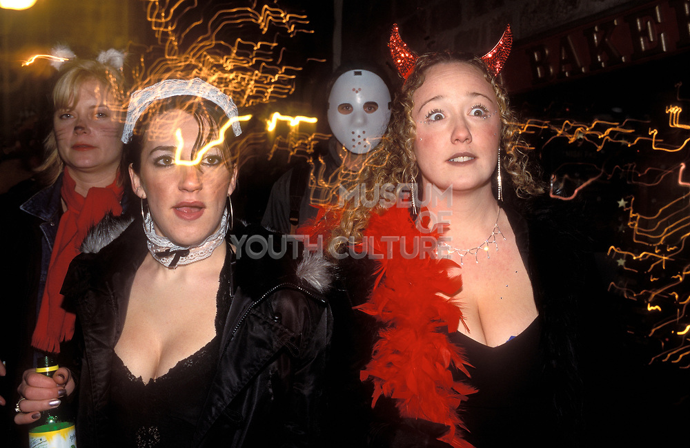 Two girls in fancy dress, one in devil horns, out on the town, UK 2004