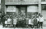 """Pilgrim Evangelical Lutheran Church (a Synodical conference black church) mission school, Birmingham, Ala. """"Our Birmingham, Alabama school."""" Dec. 1, 1927. Rev. WM Eddleman in rear."""