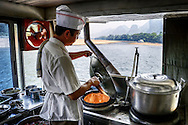 A chef is cooking a meal onboard a Lijang river boat.