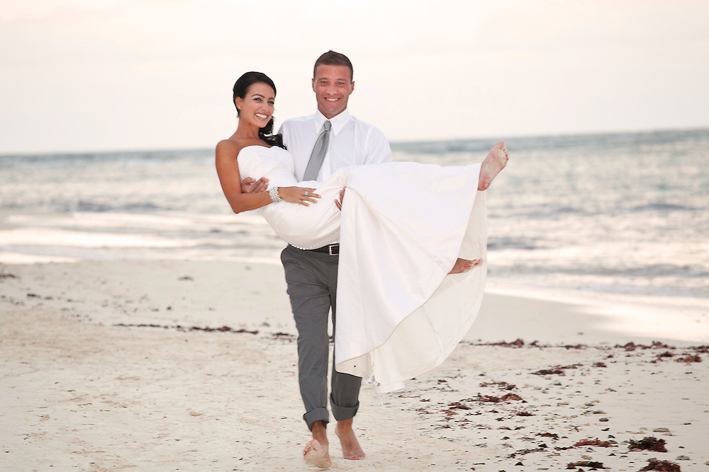 Groom carries his bride along the beach in Cancun region of Mexico