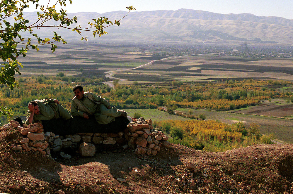 Two Peshmerga fighters rest in the early morning at their front line position over looking the town of Halabja...Halabja, Iraqi Kurdistan. 20/11/2002...Photo © J.B. Russell