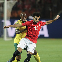 06 July 2019, Egypt, Cairo: South Africa's Sifiso Hlanti and Egypt's Mohamed Salah battle for the ball during the 2019 Africa Cup of Nations round of 16 soccer match between Egypt and South Africa at Cairo International Stadium. Photo : PictureAlliance / Icon Sport