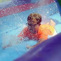 Ayden Holloway, 11, slides down the slip-n-slide Saturday at the back to school event held at Veterans park