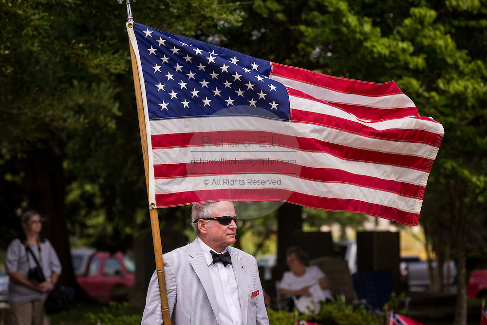 A descendant of Civil War soldiers holds the American flag at a ceremony marking Confederate Memorial Day at Magnolia Cemetery April 10, 2014 in Charleston, SC. Confederate Memorial Day honors the approximately 258,000 Confederate soldiers that died in the American Civil War.