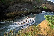 Fishing boat heading to sea between narrow rock channel, world's smallest natural navigable harbor, Depoe Bay, Oregon Coast