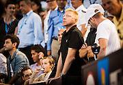Tennis legend Boris Becker - in black shirt -watches as his student - Novak Djokovic (SRB) went up against unseeded Lucas Lacko (SVK)  in day one play of the 2014 Australian Open In Melbourne. Djokovic defeated Lacko 6-3,7-6,6-1.