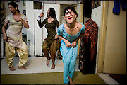 """Chabbou, K. and Kastouri (from the left),  32, 21, 16 years old, transvestites, try a dance. The Guru, Chabbou, has the assignment to educate and to teach to his childs what has learned. Transvestites people have created a community, a kind of an hierarchical staircase, based on rules handed down by generations. Evening in Lahore, Pakistan on Monday, December 01 2008.....""""Not men nor women"""". Just Hijira, Kusra. Painted lips, Kajal surrounding their eyes and colourful veils..Pakistan is today considered a strongly, foundamentalist as well, islamic country. But under its reputation, above all over the talebans' continuos advancing, stirs a completely extraneous world, a multiethnic mixed society. Transvestites make part of it, despite this would not be admitted by a strict law. Third gender, the Hijira are born as men (often ermaphrodites) or with an ambiguous genital situation, and they have their testicles and penis removed through a - often brutal - surgical operation. The peculiarity is that this operation does not contemplate the reconstruction of a female organ. This is the reason why they are not considered as men nor women, just Hijira. They are often discriminated, persecuted  and taxed with being men prostitutes in the muslim areas. The members of this chast perform dances during celebrations, especially during weddings, since it is anciently believed that an EUNUCO's dance and kiss in the wedding day brings good luck to the couple's fertility...To protect the identities of the recorded subjects names and specific .places are fictionals."""