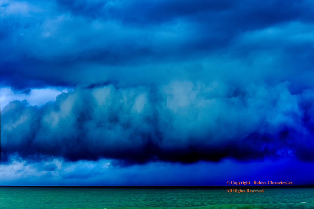 Angry Sky: An angry, dark blue storm clouds ominously pass over an emerald green Pacific Ocean, Ko Lanta – Thailand.