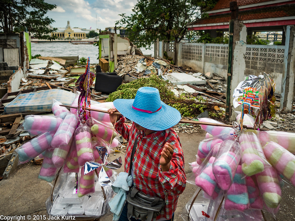 12 NOVEMBER 2015 - BANGKOK, THAILAND:   A cotton candy vendor walks through the Wat Kalayanmit neighborhood, past a house that was torn down. Fifty-four homes around Wat Kalayanamit, a historic Buddhist temple on the Chao Phraya River in the Thonburi section of Bangkok, are being razed and the residents evicted to make way for new development at the temple. The abbot of the temple said he was evicting the residents, who have lived on the temple grounds for generations, because their homes are unsafe and because he wants to improve the temple grounds. The evictions are a part of a Bangkok trend, especially along the Chao Phraya River and BTS light rail lines. Low income people are being evicted from their long time homes to make way for urban renewal.       PHOTO BY JACK KURTZ