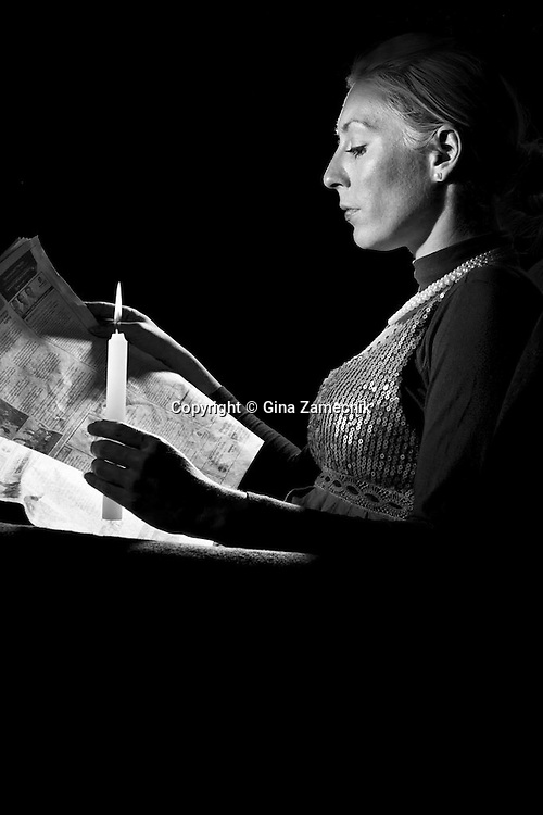 """Replication of Alfred Eisenstaedt's photo of Actress Sophia Loren reading newspaper by candlelight while in constume for role in movie """"Madame Sans Gene"""", 1961"""