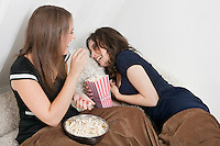 Cheerful young women eating popcorn in bed