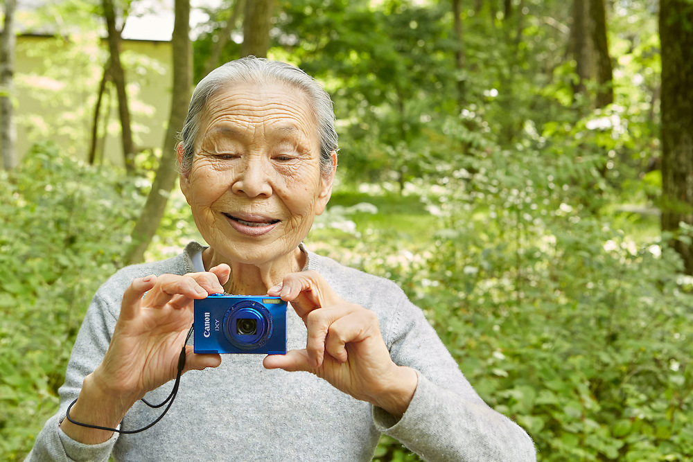 Lifestyle image of old Asian lady with point and shoot Canon camera in woods