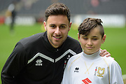 Milton Keynes Dons defender George Baldock (2) poses with the match day mascot during the EFL Sky Bet League 1 match between Milton Keynes Dons and Shrewsbury Town at stadium:mk, Milton Keynes, England on 25 February 2017. Photo by Dennis Goodwin.