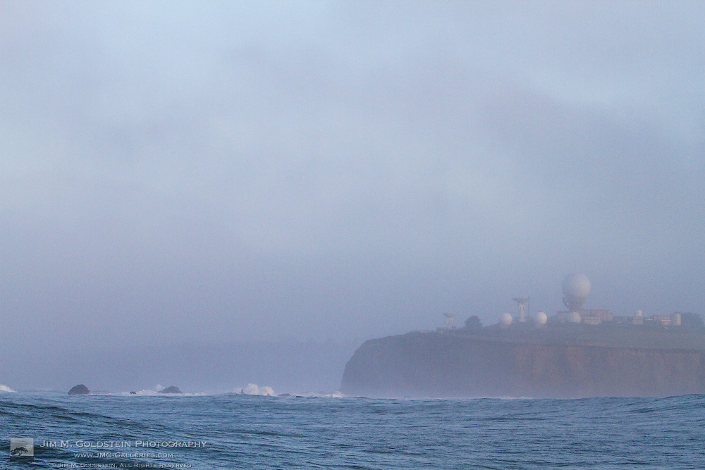 Waves crash on the rocks with fog concealing the Pillar Point Air Force station on the cliffs