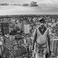 A construction worker standing on the top floor of the tallest building in Dhaka city, Bangladesh.<br /> <br /> Construction workers render a significant contribution to the growth of an economy, especially with respect to the development of a city. But socio-economic background of construction workers in Bangladesh has become worse in the absence of any formal institutions, protection laws, development plans, training centres and other types of considerable supports.