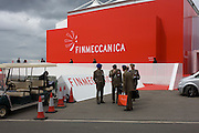 Foreign armed forces personnel leave the Finmeccanica aerospace and defence trade stand at the Farnborough Air Show, UK.