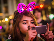 31 DECEMBER 2013 - BANGKOK, THAILAND: A woman takes pictures with her smart phone on New Year's Eve in Ratchaprasong Intersection in Bangkok. Hundreds of thousands of people pack into the Ratchaprasong Intersection in Bangkok for the city's annual New Year's Eve countdown. Many Thais go the Erawan Shrine and Wat Pathum Wanaram near the intersection to pray and make merit.     PHOTO BY JACK KURTZ
