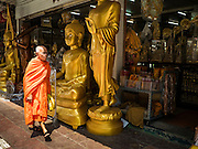 09 MARCH 2016 - BANGKOK, THAILAND: A Buddhist monk walks past statues of the Buddha for sale on Thanon Bamrung Muang in Bangkok. The street is lined with workshops that make statues of the Buddha and revered Thai Buddhist monks. Once located just outside Bangkok's city walls, it's now in the heart of the city.     PHOTO BY JACK KURTZ