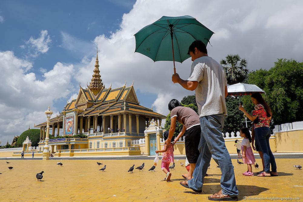 Asiatische Touristen spazieren über den Park vor königlichen Palast in Phnom Penh.