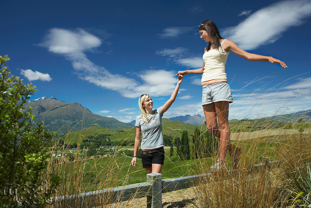 Woman helping another woman walk along fence in countryside