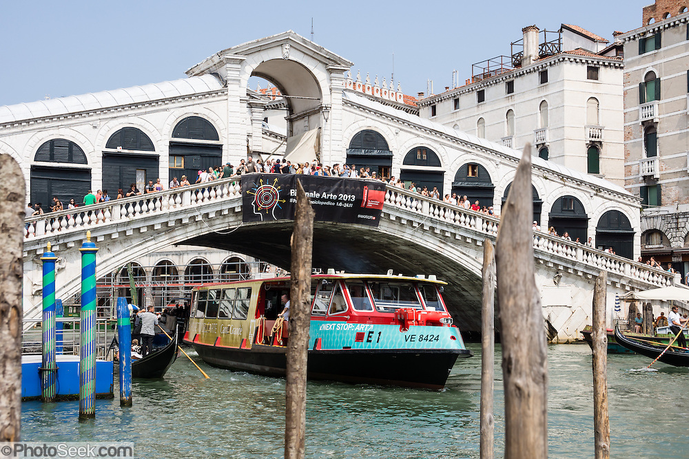 "A vaporetto (waterbus) cruises under Rialto Bridge (Ponte di Rialto, built 1591), the oldest of four bridges spanning the Grand Canal in Venice, in Italy, Europe. The single span stone bridge designed by Antonio da Pontestone is an architectural icon of Venice. In 452 AD, Attila the Hun invaded Italy, and people retreated to offshore islands called Rivo Alto (high bank), or Ri'Alto, the center of Venice. Venice/Venezia is the capital of Italy's Veneto region, named for the ancient Veneti people from the 900s BC. The romantic ""City of Canals"" stretches across 100+ small islands in the marshy Venetian Lagoon along the Adriatic Sea in northeast Italy. The Republic of Venice was a major maritime power during the Middle Ages and Renaissance, a staging area for the Crusades, and a major center of art and commerce (silk, grain and spice trade) from the 1200s to 1600s. The wealthy legacy of Venice stands today in a rich architecture combining Gothic, Byzantine, and Arab styles. Venice and the Venetian Lagoons are on the prestigious UNESCO World Heritage List."