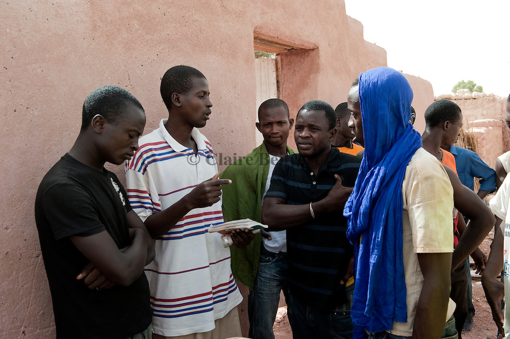 Ousmane, Zacharia, and other African migrants speaking about their coming trip to Libya in front the ghetto in Dirkou