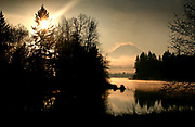 As the sun rises over Lake Tapps, near Auburn, the fog breaks for a few moments at this scene of the lake Mt. Rainier.  (Ellen M. Banner / The Seattle Times)