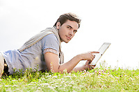 Side view of young man using digital tablet while lying on grass against clear sky