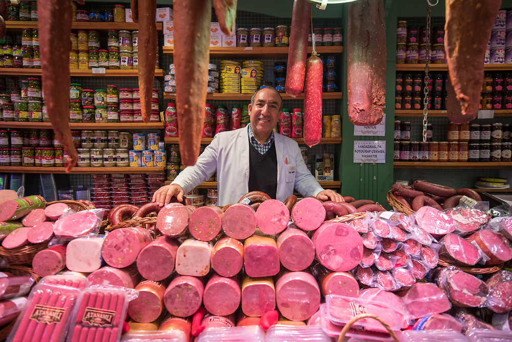 A smiling adult male merchant stands behind counter full of various types of meat for sale at Istanbul Spice bazaar in Turkey