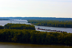 October 2009: View of the Savannah bridge over the Mississippi River, and a tug boat pushing several barges from an outlook in the Mississippi Palisades State Park. Sights to see in and around Galena Illinois. This image was produced in part utilizing High Dynamic Range (HDR) or panoramic stitching or other computer software manipulation processes. It should not be used editorially without being listed as an illustration or with a disclaimer. It may or may not be an accurate representation of the scene as originally photographed and the finished image is the creation of the photographer.