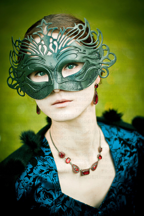 Woman with brown hair and green eyes wearing a period blue dress with a carnival black mask and a red necklace