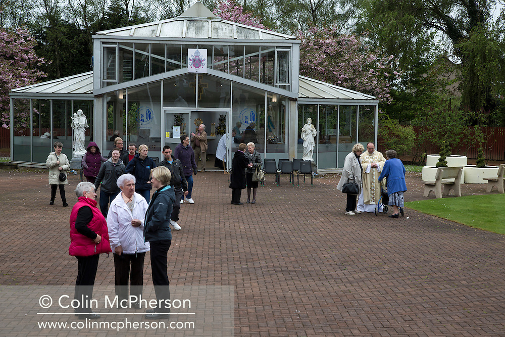 'Untitled, 2014' from the project 'The Fall and Rise of Ravenscraig' by photographer Colin McPherson.<br /> <br /> The photograph shows visitors at the Carfin Grotto after a service in one of the site's chapels. The Grotto is located at the northern end of the former steelworks at Ravenscraig.<br /> <br /> This project, photographed in 2014, looks at the topography of the post-industrial landscape at Ravenscraig, the site until its closure in 1992 of the largest hot strip steel mill in western Europe. In its current state, Ravenscraig is one of the largest derelict sites in Europe measuring over 1,125 acres (4.55 km2) in size, an area equivalent to 700 football pitches or twice the size of Monaco. It is currently being developed with a mix of housing, retail and the home of South Lanarkshire College and the Ravenscraig Regional Sports Facility.
