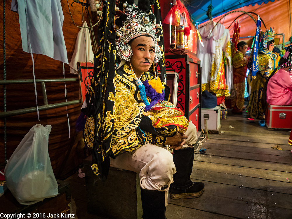 17 FEBRUARY 2016 - BANGKOK, THAILAND: Chinese opera performers wait for the show to start during a performance in Bangkok. The small troupe travels from Chinese shrine to Chinese shrine performing for a few nights before going to another shrine. They spend about half the year touring in Thailand and the other half of the year touring in Malaysia. Members of the troupe are paid about 5,000 Thai Baht per month (about $140 US). Chinese opera was once very popular in Thailand, where it is called Ngiew. It is usually performed in the Teochew language. Millions of Chinese emigrated to Thailand (then Siam) in the 18th and 19th centuries and brought their culture with them. Recently the popularity of ngiew has faded as people turn to performances of opera on DVD or movies. There are still as many 30 Chinese opera troupes left in Bangkok and its environs. They are especially busy during Chinese New Year and Chinese holiday when they travel from Chinese temple to Chinese temple performing on stages they put up in streets near the temple, sometimes sleeping on hammocks they sling under their stage. Most of the Chinese operas from Bangkok travel to Malaysia for Ghost Month, leaving just a few to perform in Bangkok.     PHOTO BY JACK KURTZ