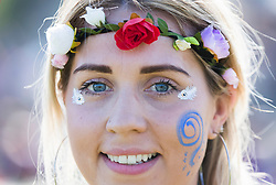 © Licensed to London News Pictures. 05/05/2018. Chalton, UK. 28 year old Sara Miles from Havant wears flowers in her hair as she enjoys the sunshine during the Beltain Festival at Butser Ancient Farm in Hampshire. Over two thousand people have gathered to witness the ancient Beltain Celtic celebration of summer - which culminates in the burning of a giant Wickerman figure  Photo credit: Peter Macdiarmid/LNP